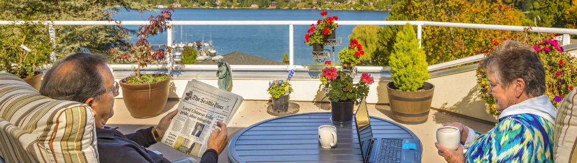 residents reading the newspaper from patio apartment with a view of the lake