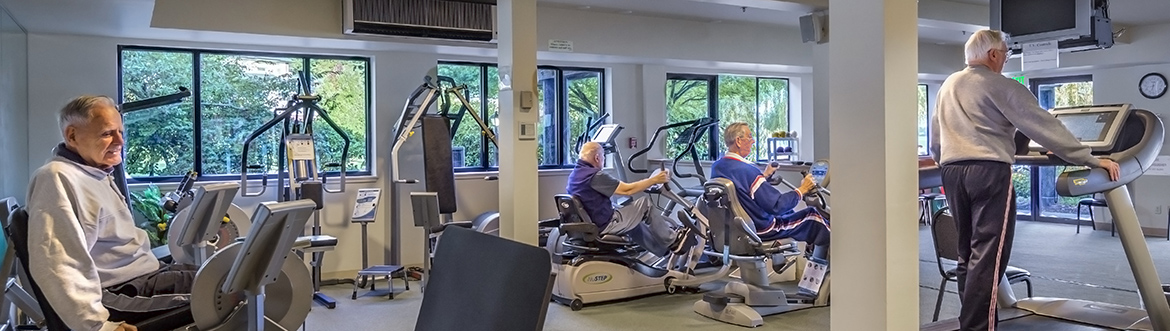 Seniors working out on stationary bikes at the fitness center